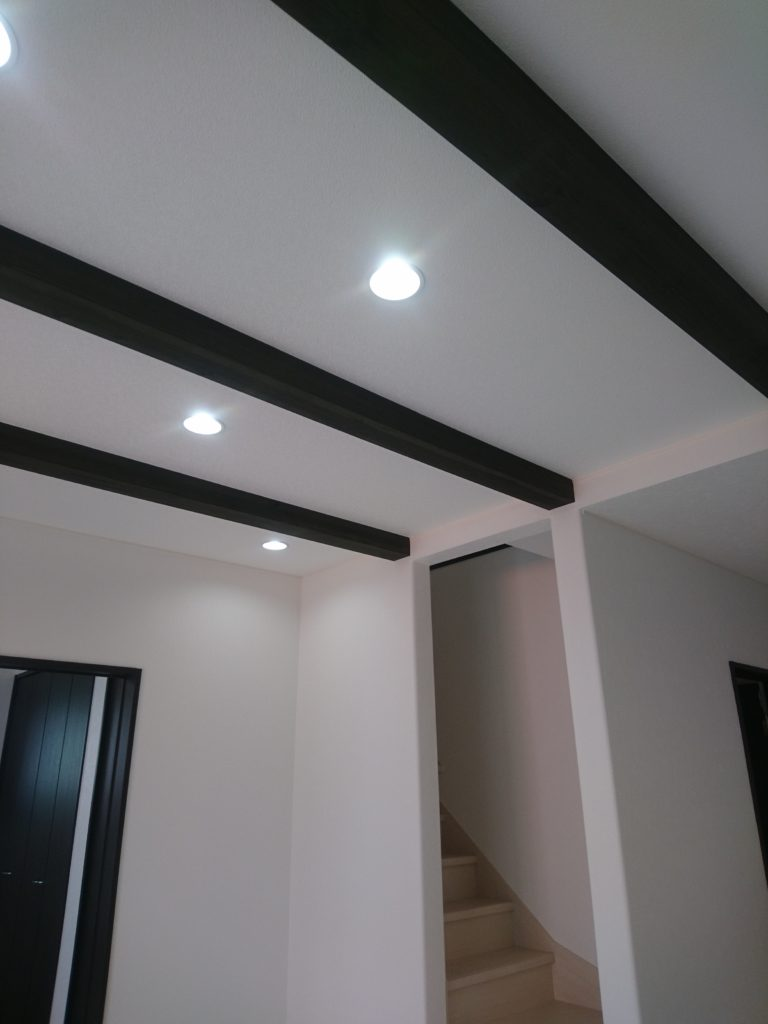 白いクロスに映える、シックな色の梁見せ天井がお洒落なリビング